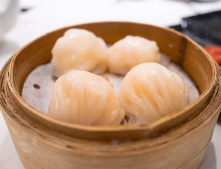 4 delicious har gao in a bamboo steamer at a dim sum restaurant in hong kong
