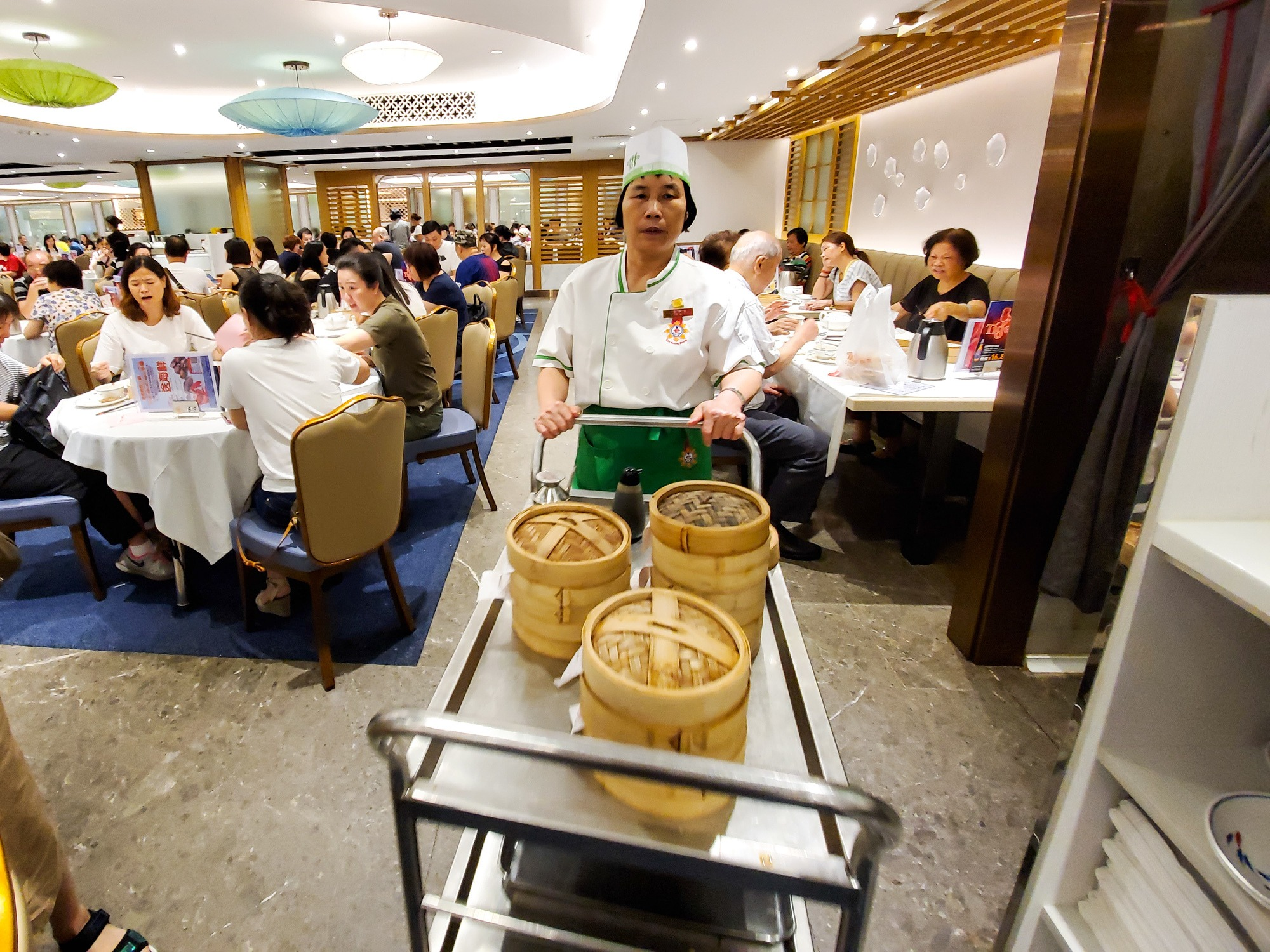 The dim sum cart is being pushed by a local server at a dim sum restaurant in Hong Kong